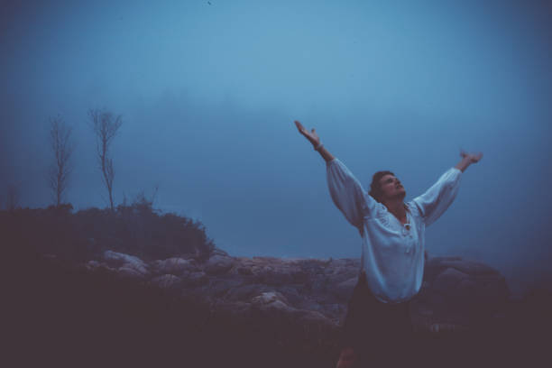 Woman Raising Arms to Sky in Despair or Grief in Foggy Landscape stock photo