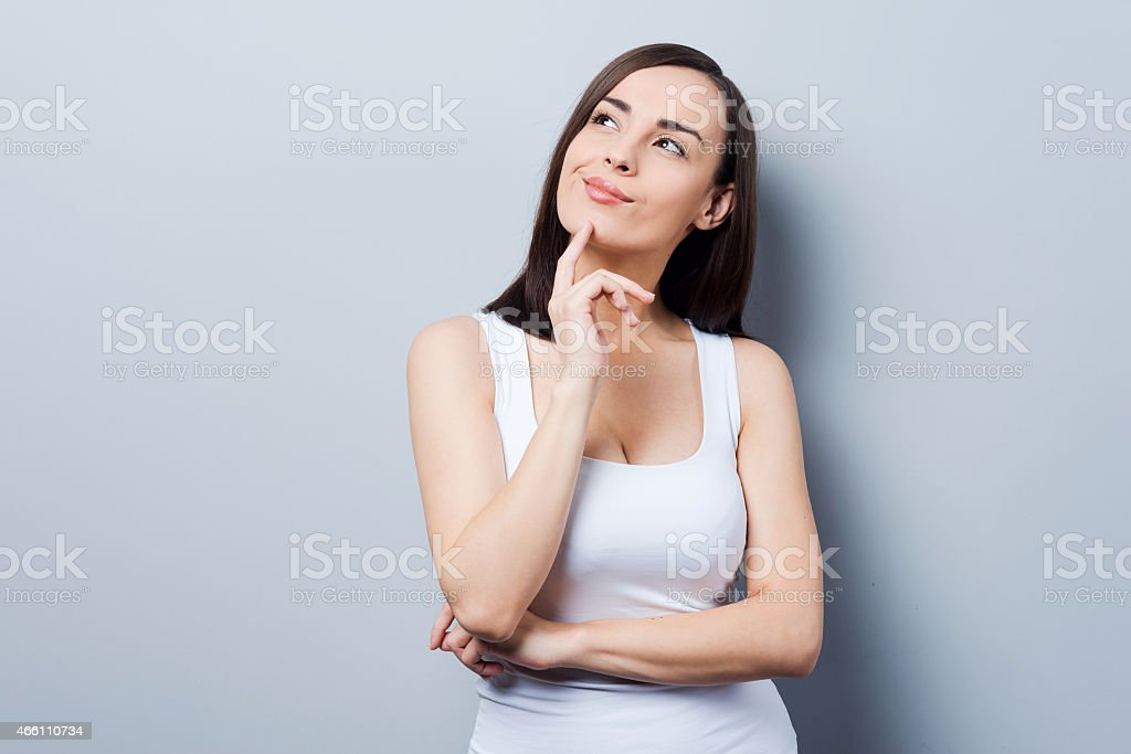 Woman raising her hand to her chin as in deep thought stock photo