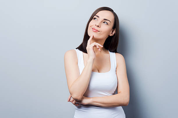woman raising her hand to her chin as in deep thought - uncertainty stock pictures, royalty-free photos & images