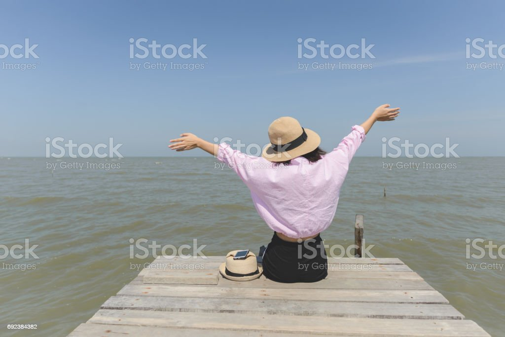 Woman raising her hands and siiting on wooden pier facing to sea view and blue sky stock photo