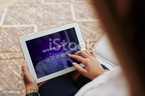 Woman rating service and leaving feedback via application on tablet computer