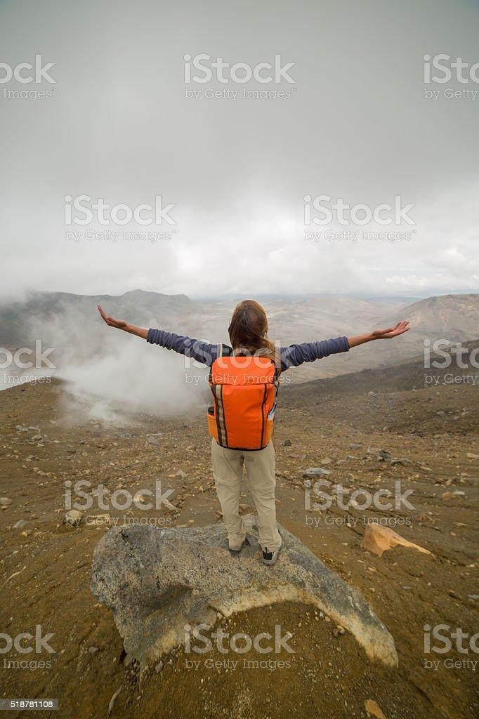 Woman reaches mountain top, outstretches arms stock photo