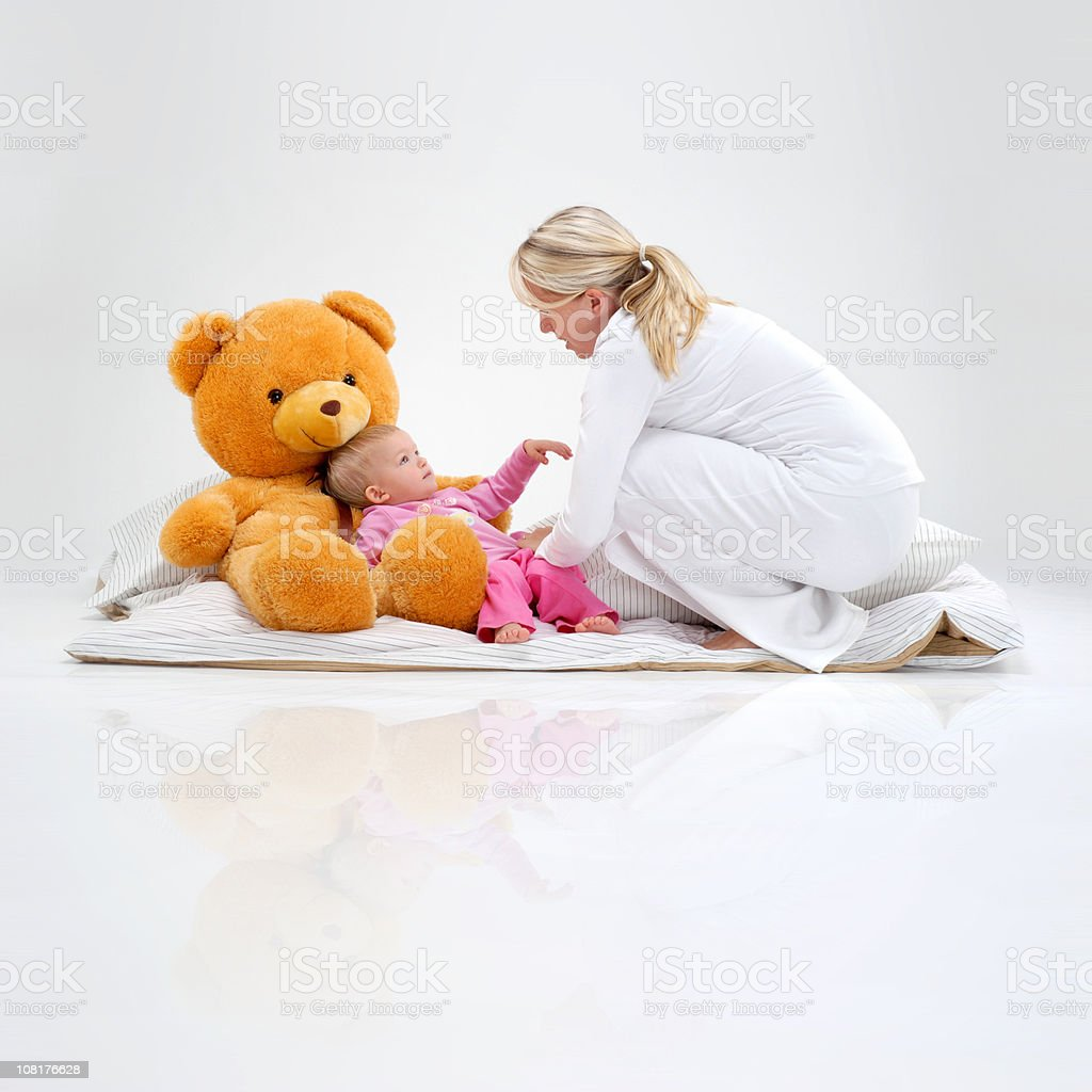 Woman Reaching Down to Little Girl Lying with Teddy Bear royalty-free stock photo