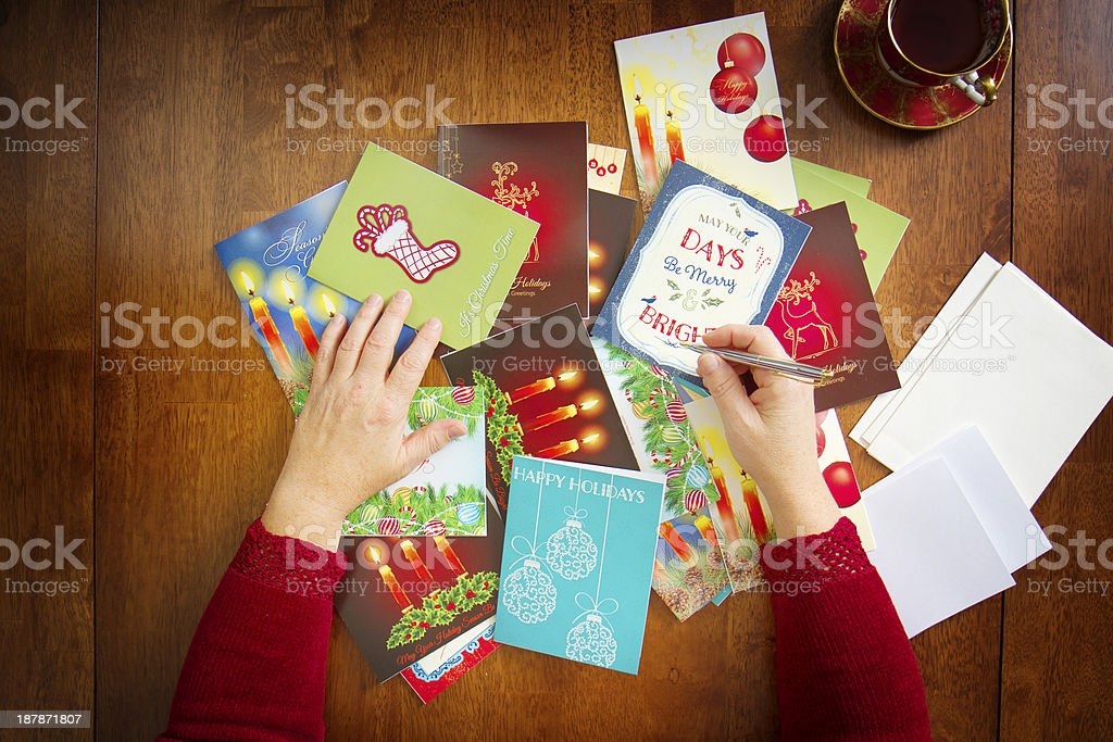 Woman Reaching For Holiday Cards On Table stock photo