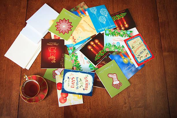 frau greifen für den urlaub karten auf den tisch - weihnachtskarte stock-fotos und bilder