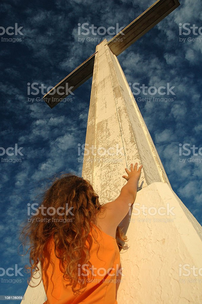 Woman Reaching Hands Up Towards Cross royalty-free stock photo