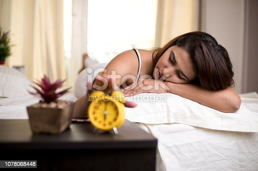 istock Woman reaching out for alarm clock 1078068448