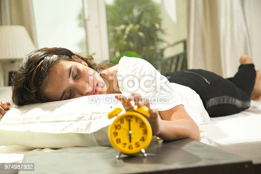 istock Woman reaching out for alarm clock 974987932