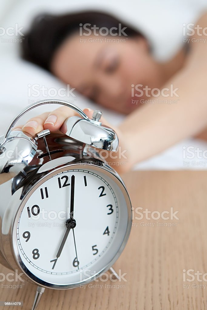 Woman reaching out for alarm clock royalty free stockfoto