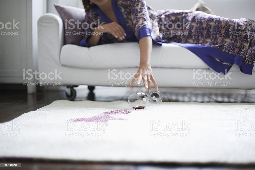Woman Reaching Toward Spilled Wine Glass On Rug stock photo