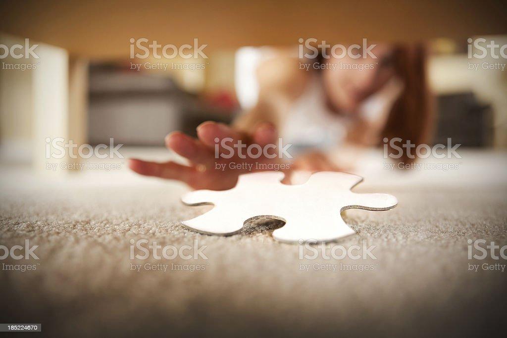 Frau greifen unter Tisch für fehlende Puzzleteil – Foto