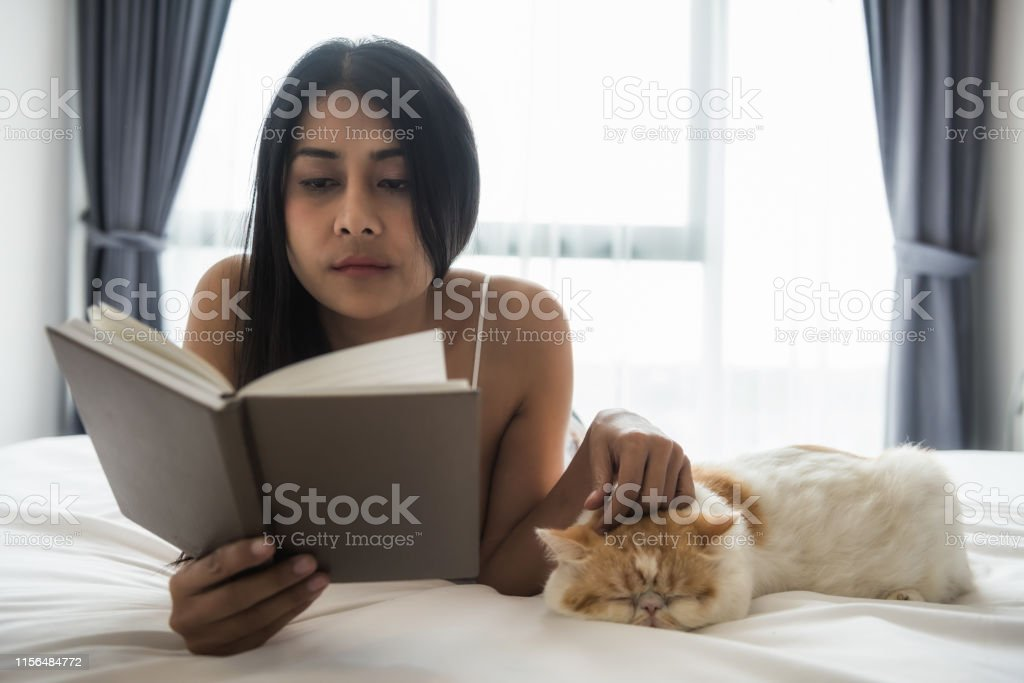 Asian tan woman read fiction text book on white bed and play with...
