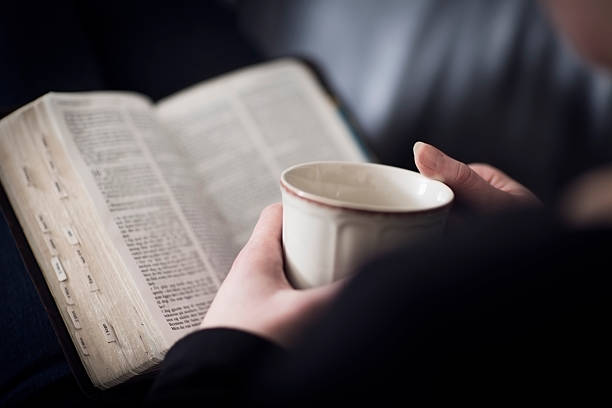 Woman Read the Bible and Drink Tea or Coffee stock photo