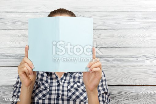 istock Woman reading a book and covering her face 485252036