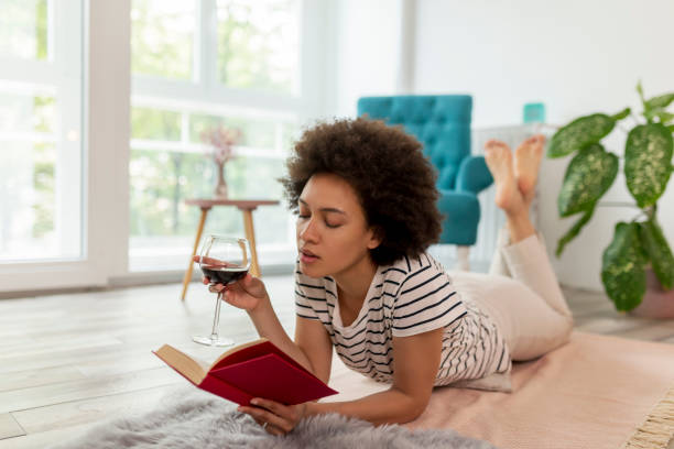 Woman reading a book and drinking wine stock photo
