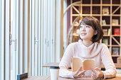 カフェで本を読んでいる女