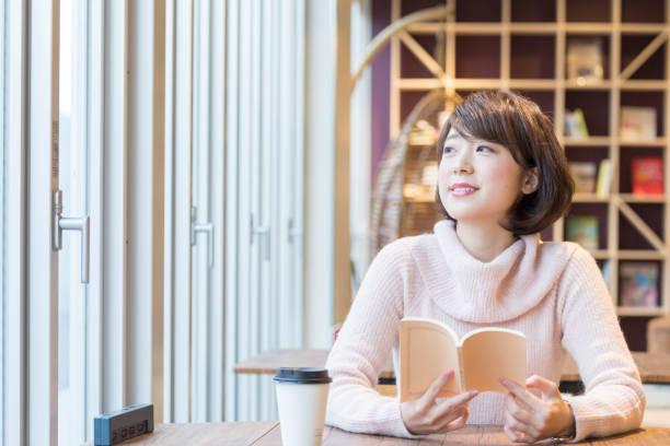 カフェで本を読んでいる女 ストックフォト