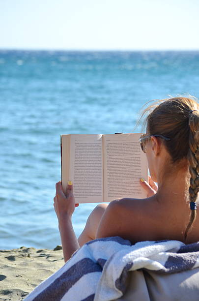 Woman Reading a book at the beach stock photo