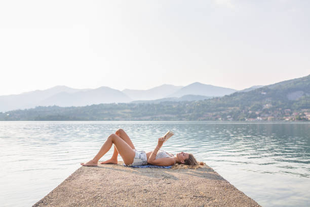 Woman reading a book by the lake stock photo