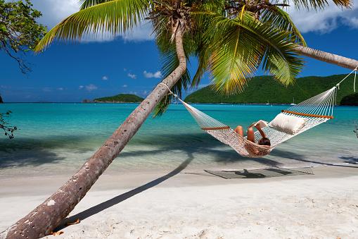 woman reading a book in a hammock on a tropical beach in the Caribbean, Maho Bay, St. John