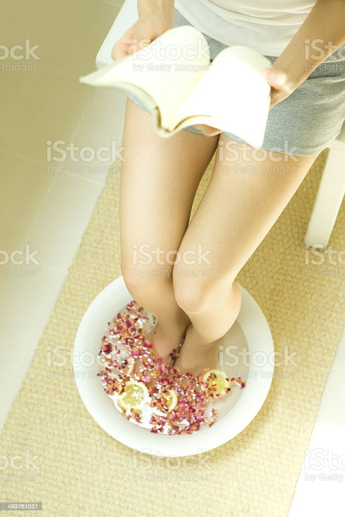 Woman Reading A Book In Footbath Of Rose And Lemon Stock Photo