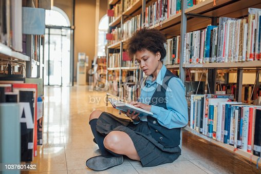 istock Woman reading a book in the library 1037601432