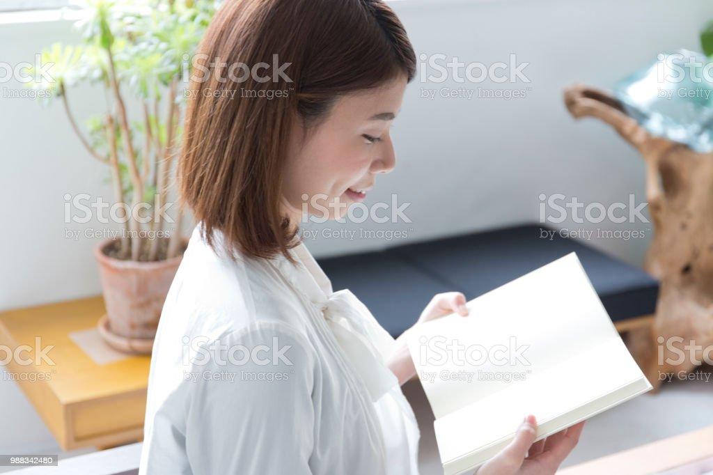 部屋で本を読んでいる女 ストックフォト