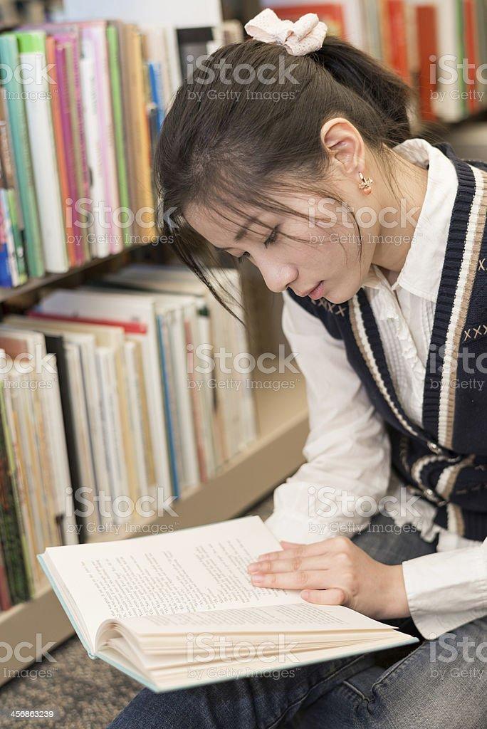 Woman reading a book near bookshelf royalty-free stock photo