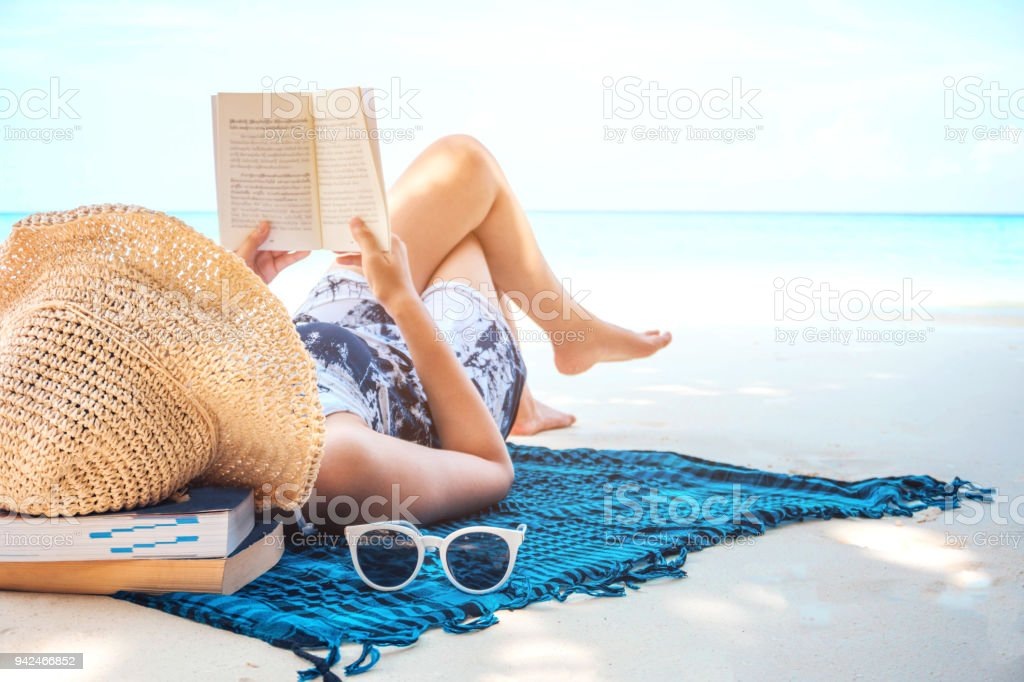 Woman  reading a book on the beach in free time summer holiday stock photo