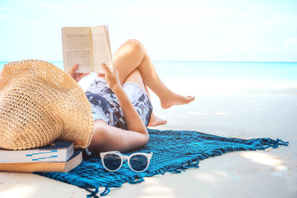 woman  reading a book on the beach in free time summer holiday - vacanze foto e immagini stock