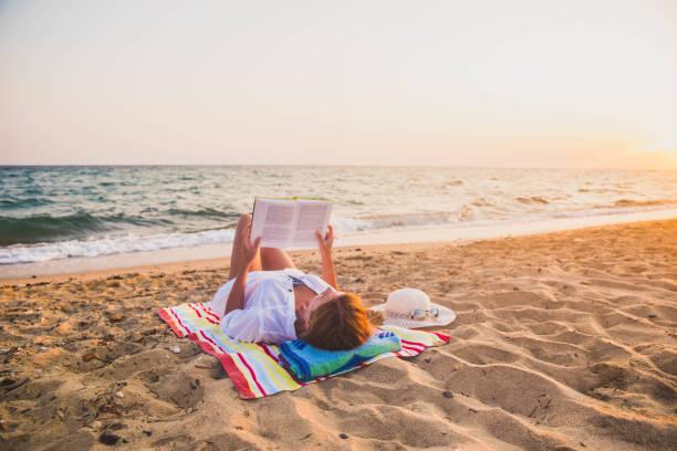 해변에서 책을 읽는 여자 - 비치 타월 뉴스 사진 이미지