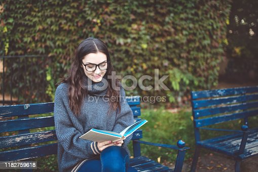 521911045istockphoto Woman reading a book on the bench in a park 1182759618