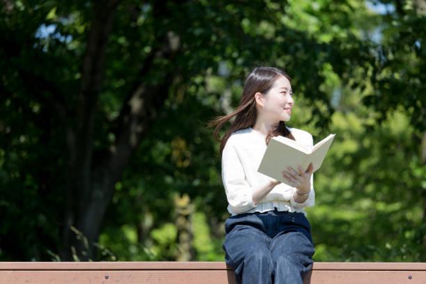 屋外の本を読んでいる女 ストックフォト