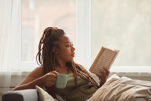 African young woman lying on sofa drinking coffee and reading an interesting book at home