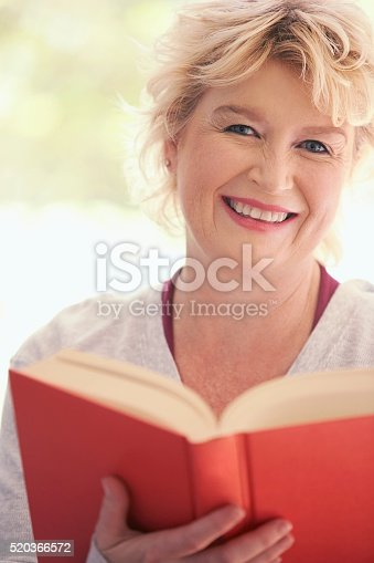 istock Woman reading a book 520366572