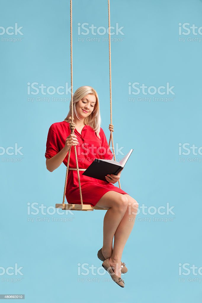 Woman reading a book seated on a swing stock photo