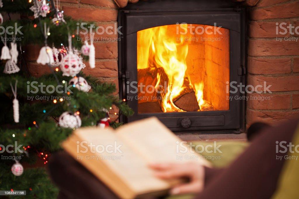 Frau liest ein Buch vor dem Kamin sitzen – Foto
