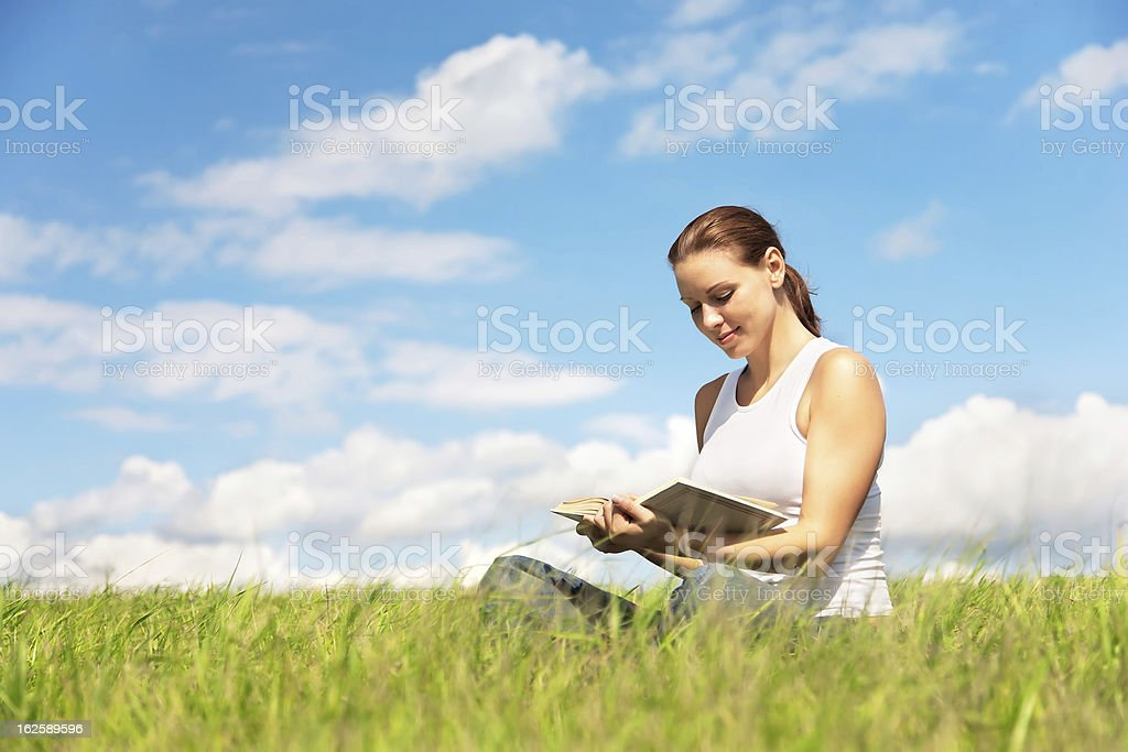 woman reading a book sitting on the grass royalty-free stock photo