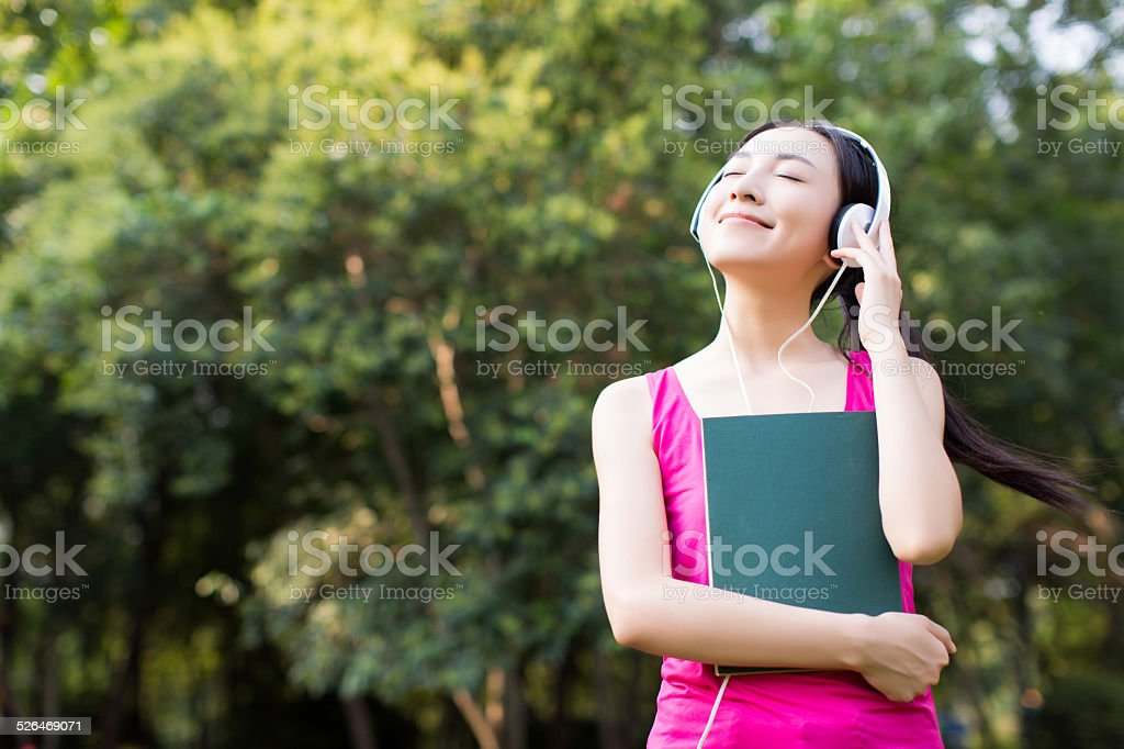 woman reading a book while listening music in park stock photo
