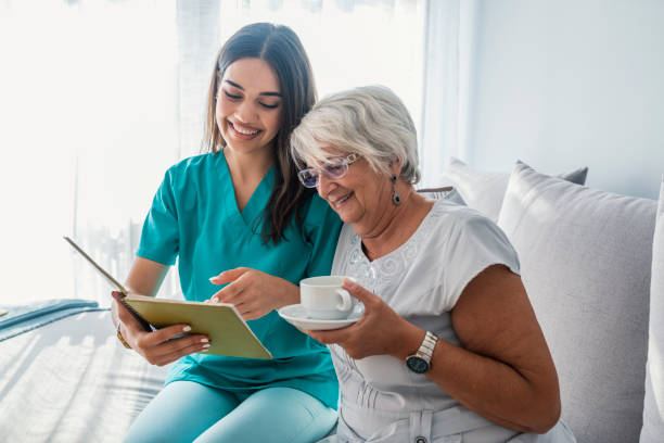 woman reading a book while sitting with happy grandmother drinking tea - infermiera personale medico foto e immagini stock