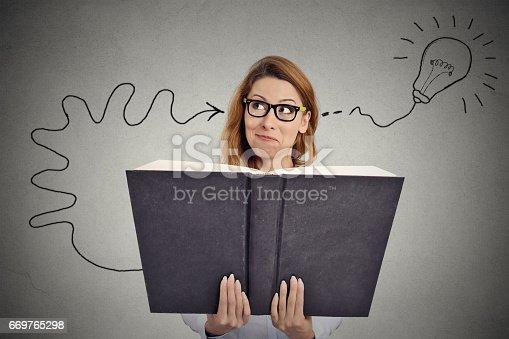 istock Woman reading a huge book has a good idea 669765298