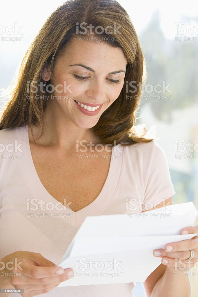 A woman reading a letter and smiling  stock photo