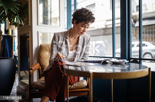 Young woman reading a magazine while sitting at restaurant table. Caucasian female in casuals relaxing at a cafe.