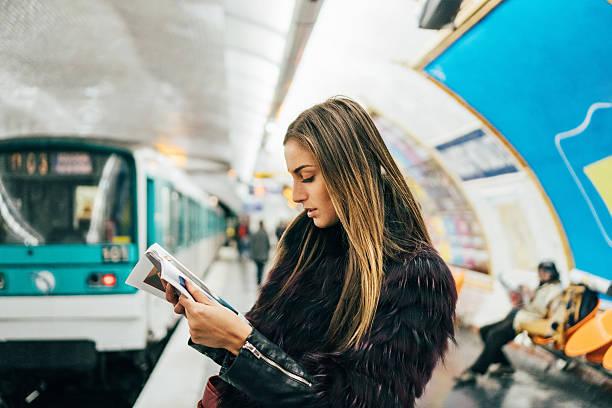 mujer leyendo una revista en la estación de metro parisino - moda parisina fotografías e imágenes de stock
