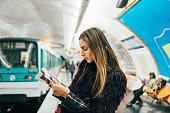 Woman reading a magazine in Parisian metro station