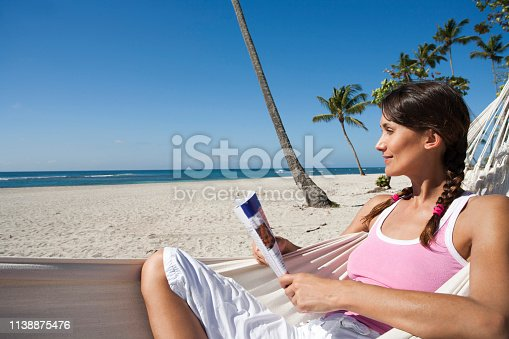 woman reading a magazine in a hammock on the beach