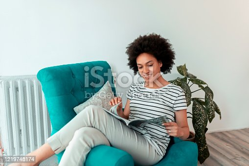Beautiful young mixed race woman sitting in an armchair, reading a magazine and relaxing at home