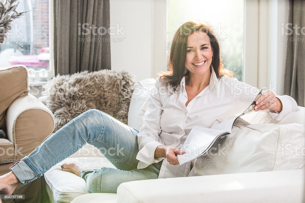 Woman reading a magazine smiling at the camera stock photo