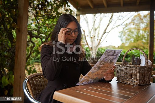 A pretty young woman sitting at an outdoor cafe table reading a menu.