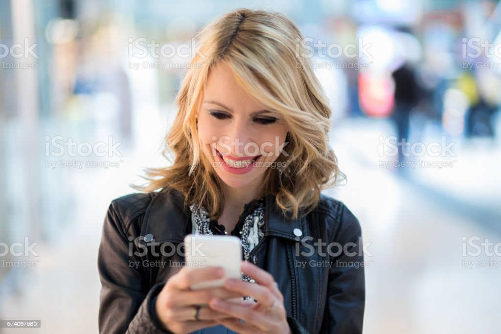Woman reading a message on her phone royalty-free stock photo